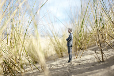 Businessman figurine standing on sand dune, looking at distance - FLAF00016