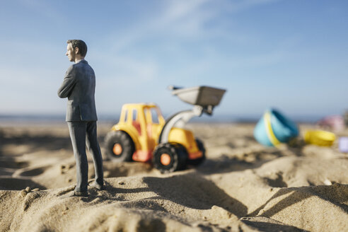 Businessman figurine standing on sand with toy digger, investment in home ownership - FLAF00019
