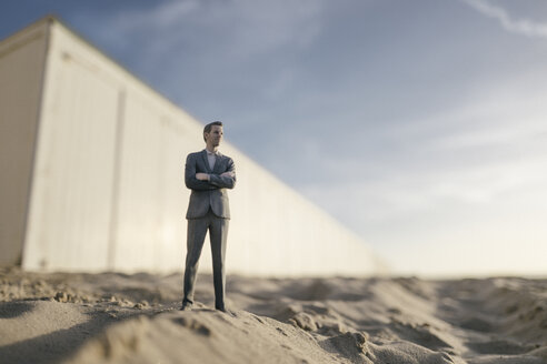 Businessman figurine standing on sand in front of building - FLAF00022