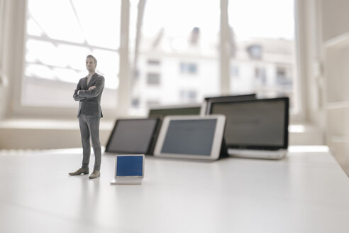 Businessman figurine standing on desk, facing mobile devices - FLAF00037