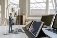 Businessman figurine standing under glass bell on desk, facing mobile devices - FLAF00040