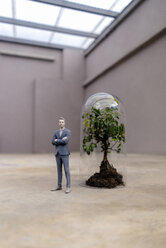 Businessman figurine standing by tree under a bell jar - FLAF00043