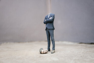Headless businessman figurine standing on cocrete - FLAF00046