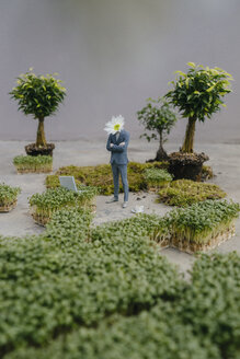 Businessman figurine with flower head standing park - FLAF00049