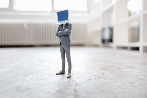 Businessman figurine with laptop head standing on concrete - FLAF00052