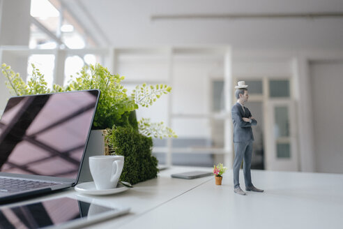 Businessman figurine standing on desk, balancing a cup of coffee on top of his head - FLAF00058