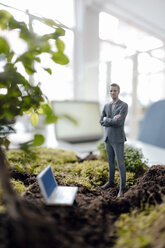 Businessman figurine with laptop standing on green moss - FLAF00064