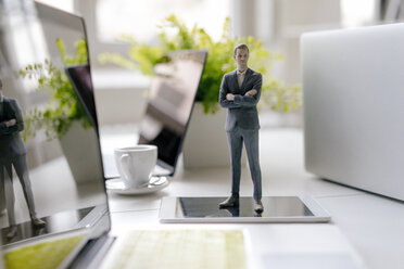 Businessman figurine standing on a desk with mobile devices and a cup of coffee - FLAF00067