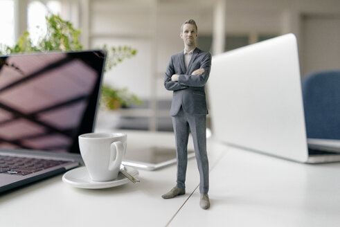 Businessman figurine standing on a desk with mobile devices and a cup of coffee - FLAF00070