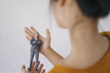 Young woman holding miniature figurine of her boss - FLAF00073