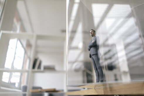 Businessman figurine standing in modern office, looking through glass pane - FLAF00079