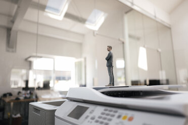 Businessman figurine standing on copy machines in  modern office - FLAF00082