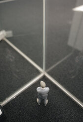 Businessman figurine standing between glass panes - FLAF00085