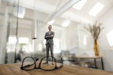 Businessman figurine standing behind glasses on desk in modern office - FLAF00088