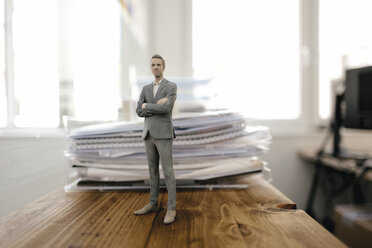 Businessman figurine standing on desk with files - FLAF00091