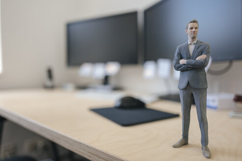 Businessman figurine standing on desk in modern office - FLAF00094
