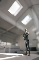 Businessman figurine standing on desk in modern office - FLAF00097