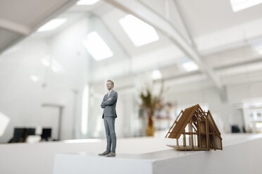 Businessman figurine standing on desk next to architectural model - FLAF00100