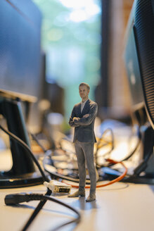 Businessman figurine standing amidst computer cables - FLAF00106