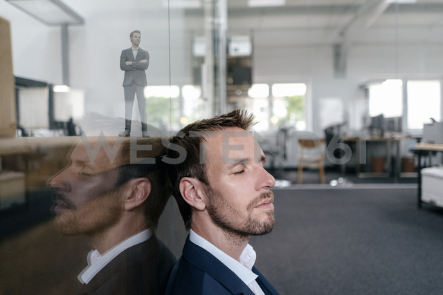 Businessman sitting in his office with his 3D portrait behind a glass pane - FLAF00109 - Flamingo/Westend61