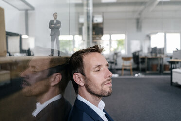 Businessman sitting in his office with his 3D portrait behind a glass pane - FLAF00109