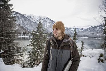 Happy man in alpine winter landscape with lake - SUF00397
