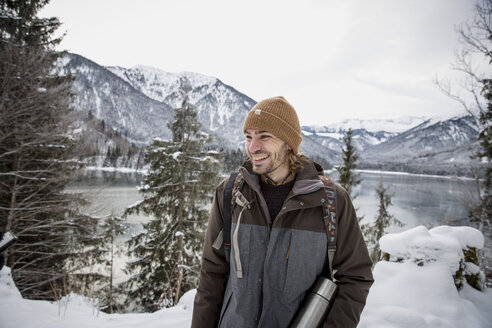 Happy man in alpine winter landscape with lake - SUF00397