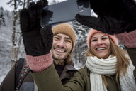 Happy couple taking a selfie in winter landscape - SUF00400