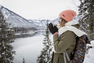 Young woman with hot drink standing in alpine winter landscape with lake - SUF00403
