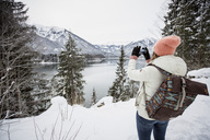 Young woman taking a picture in alpine winter landscape with lake - SUF00406