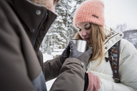 Couple sharing hot drink outdoors in winter - SUF00412
