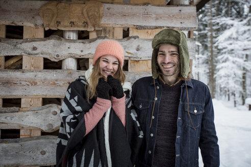 Portrait of happy couple in front of wood pile outdoors in winter - SUF00418