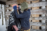 Happy couple in front of wood pile outdoors in winter - SUF00421