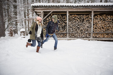 Happy couple running in front of wood pile outdoors in winter - SUF00424