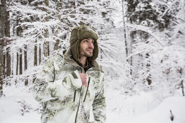 Man in camouflage jacket in winter forest - SUF00427