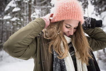 Smiling young woman outdoors in winter - SUF00430