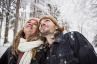 Smiling couple in winter forest watching snow fall - SUF00436