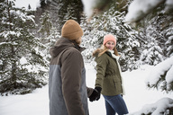 Couple walking in winter forest - SUF00439