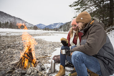Couple on a trip in winter having a break at camp fire - SUF00445