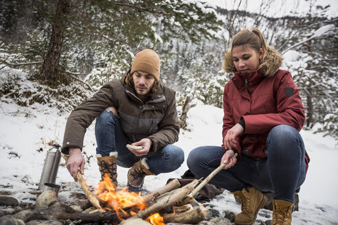 Couple on a trip in winter having a break at camp fire - SUF00448
