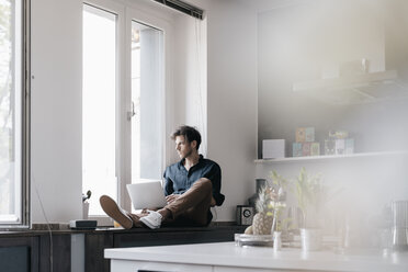 Young man with laptop sitting on window sill in a loft looking out of the window - KNSF03419