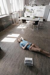 Pensive man lying on the floor in a loft - KNSF03428