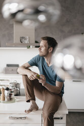Pensive man sitting on kitchen counter looking at distance - KNSF03443