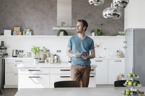 Man with tablet standing in the kitchen looking at distance - KNSF03452