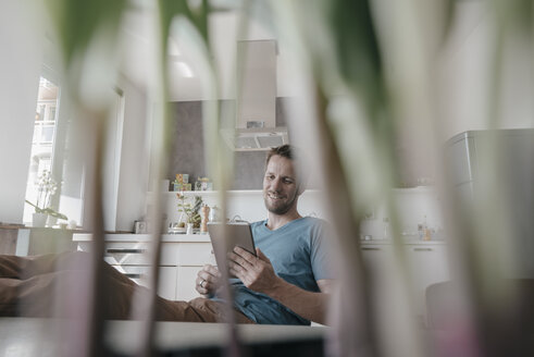 Man sitting at table in the kitchen looking at tablet - KNSF03455