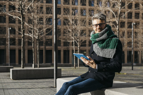Businessman with tablet sitting on bench in the city in winter - JRFF01498