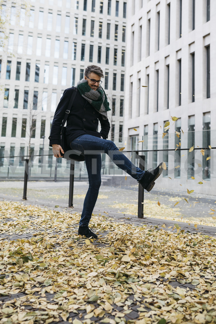Businessman playing with autumn leaves in the city - JRFF01504 - Josep Rovirosa/Westend61