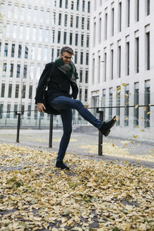 Businessman playing with autumn leaves in the city - JRFF01504
