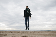 Man jumping on the beach in winter - JRFF01516