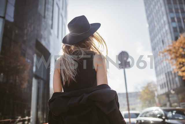 Back view of woman with hat dressed in black - KMKF00136